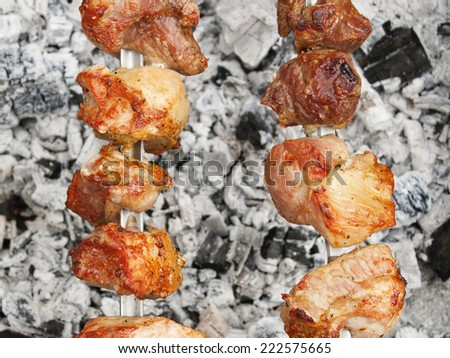 Shashlik (shish kebab) prepared on the metal skewers over charcoal with ash outdoors - stock photo