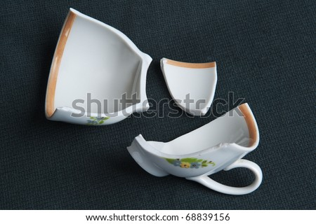 Shattered coffee cup on a black cloth - stock photo