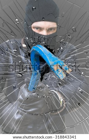 Shattered glass. Burglar or thief masked with balaclava is breaking glass with crowbar. - stock photo