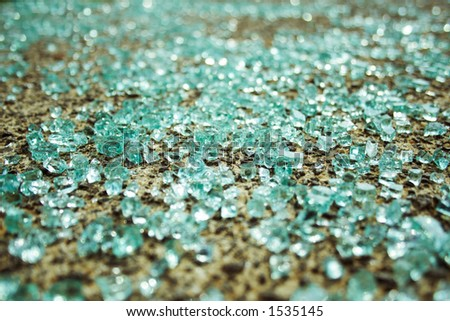 Shattered glass from a car window lays scattered on the sidewalk. - stock photo