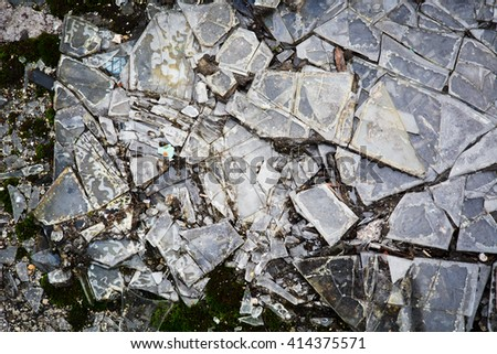 Shattered glass on the ground. Broken pieces of glass, dirt, soil and moss background stock photo. - stock photo