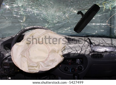 Shattered glass with airbags deployed in a wrecked car.