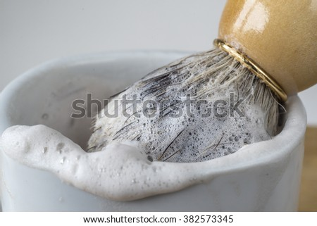 Shaving brush and bowl with foaming soap - stock photo