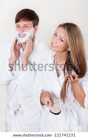 Shaving cream applied on face with white robe on. - stock photo