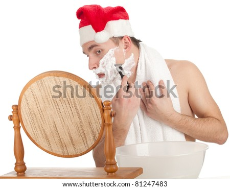 shaving handsome young man with foam and razor in red Christmsa hat - stock photo