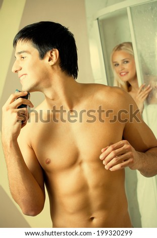 Shaving man and young woman at bathroom - stock photo