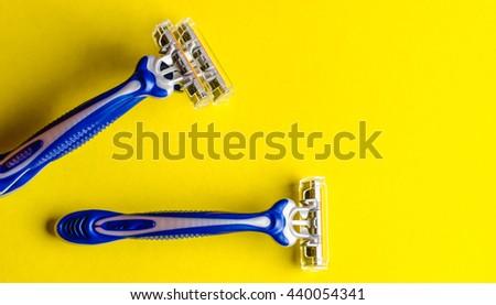 shaving razor on a yellow background - stock photo