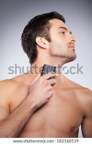 Shaving with electric shaver. Cropped image of handsome young man shaving his face with electric shaver while standing isolated on grey background - stock photo