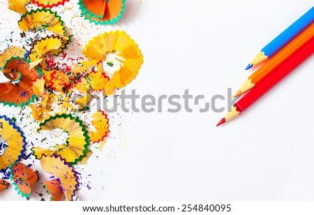 shavings and colored pencils on white background with copy space - stock photo