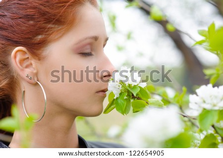 she breathes in the scent of flowers - stock photo