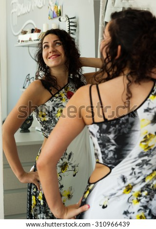 She can not hold back the joy of looking in the mirror at a new dress - stock photo