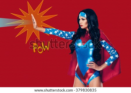 She can stop any crime. Side view of beautiful young woman in superhero costume shooting a beam from her hand while standing against red background  - stock photo