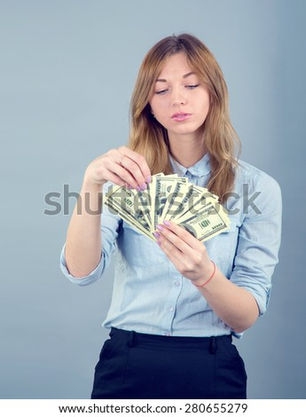 She counts the money. Girl student or a young business woman holding money in US dollars, on blue background. Female holding US dollars. Young beautiful woman with us dollar money in hand, copy space - stock photo