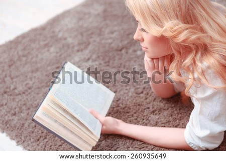 She found a peaceful place to read. Top view of confident female student reading a book while lying on the carpet - stock photo