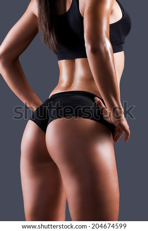 She got perfect buttocks. Rear view of beautiful young sporty woman with perfect buttocks holding hands on hip while standing against grey background - stock photo