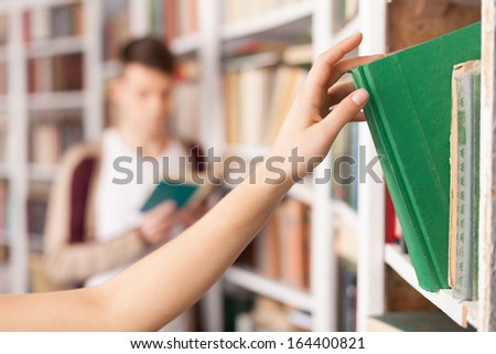 She has got the book she needs. Someone taking a book from the book shelf while young man reading on the background - stock photo