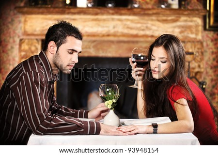 She hold his hand while they sitting at table and drinking wine near fireplace, focus on male - stock photo