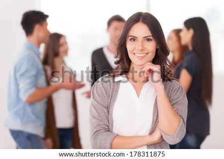 She is a team leader. Confident young woman holding hand on chin and smiling while group of people communicating on background - stock photo