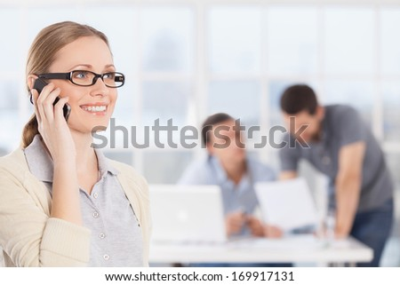 She is always in touch. Cheerful young businesswoman in casual wear talking on the phone and smiling while her colleagues communicating on the background - stock photo