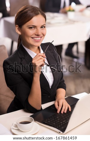 She is always in touch. Cheerful young woman in formalwear sitting at the table and talking on the phone while man sitting on background - stock photo