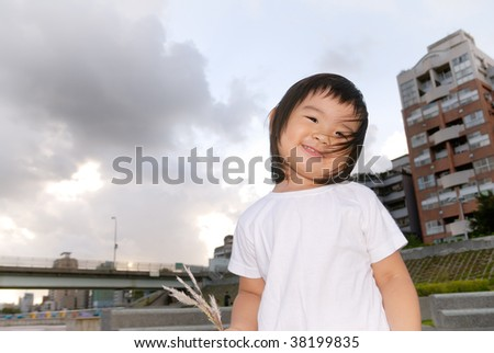 She is an East Asian gabby baby in front of apartment in the outdoor. - stock photo