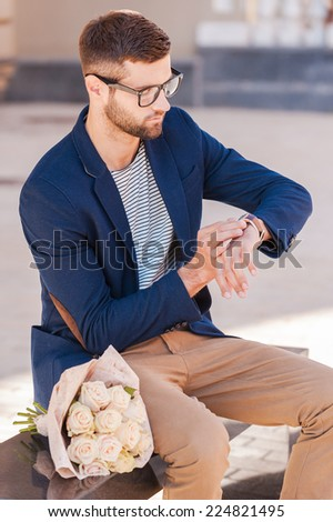 She is late again. Worried young man in smart jacket looking at his watch while sitting on the bench with bouquet of roses laying near him  - stock photo