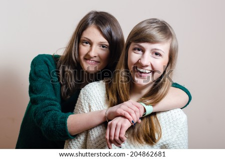 She is my best friend who I can trust: 2 girl friends having fun & good time hugging happy smile looking at camera on white or light wall copy space background closeup portrait picture - stock photo