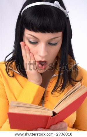 she is reading a book and she is surprised - stock photo