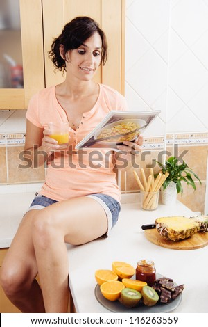 She is reading a magazine during her healthy breakfast