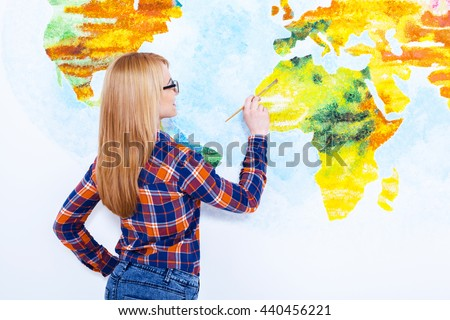 She know how to do it. Closeup of an attractive  young woman painting the wall - stock photo
