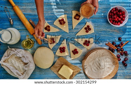 She lays cherry filling over the dough sprinkles brown sugar, it will be gentle bagels - stock photo