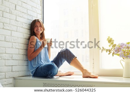 She looks delighted, happy and fully relaxed while sitting on the window-sill and drinking a cup of coffee
