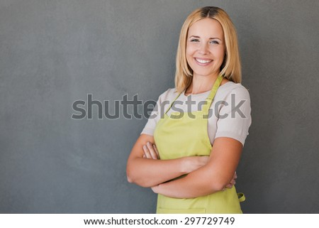 She loves her job. Smiling mature woman in green apron keeping arms crossed and looking at camera while standing against grey background  - stock photo