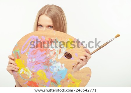 She loves the art. Young beautiful woman looking over the palette and holding paintbrush while standing isolated against white background - stock photo