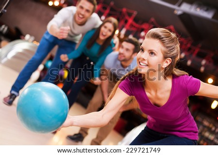 She loves this game. Beautiful young women throwing a bowling ball while three people cheering   - stock photo