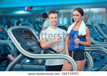 She loves training. Attractive young woman in sports clothing holding a bottle of water while standing on the treadmill with  her instructor showing his thumb up - stock photo