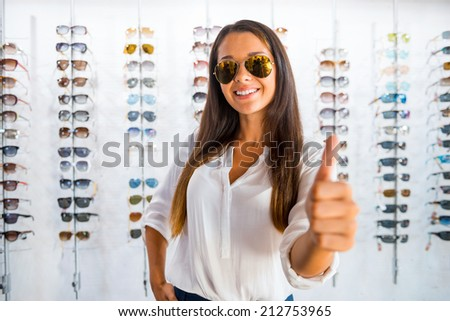 She made a right choice. Beautiful young woman in sunglasses showing her thumb up and smiling while standing in optic store  - stock photo