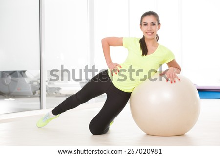 She make exercise with pilates ball on floor. Beautiful sporty woman posing for camera in sport gym. - stock photo