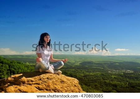 She meditates on the edge of a cliff