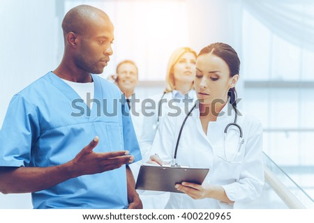 She need an expert advice.. Group of confident doctors moving downstairs while two of them discussing something and gesturing - stock photo