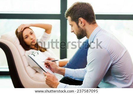 She needs an expert advice. Frustrated young woman sitting at the chair and holding hand on head while young man sitting close to her and writing something in his clipboard  - stock photo