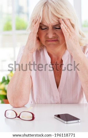 She needs help. Depressed senior woman holding head in hands and keeping eyes closed while sitting at the table with mobile phone laying on it