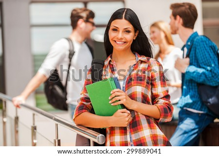 She never skips any class. Happy young woman holding books and looking at camera while her friends standing in the background   - stock photo