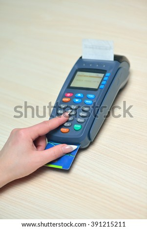 She put a credit card in payment terminal and enters the PIN code - stock photo