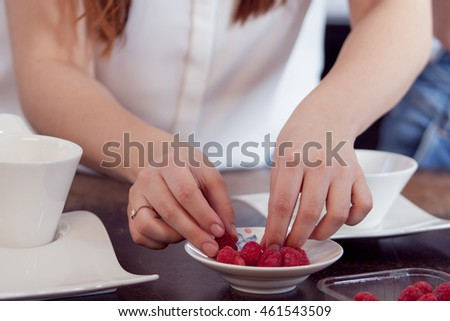 She puts raspberries on small saucer, close-up