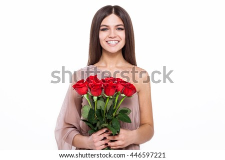 She's in love with her flowers. Attractive young woman holding a  bunch of roses and smiling into camera  isolated on white background. - stock photo