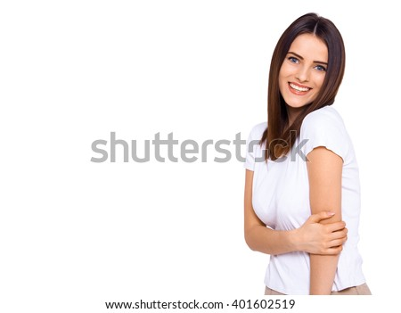 She's on the shy side. Shot of an attractive young woman smiling shyly on a white background - stock photo