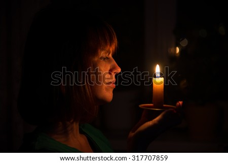 She shines a candle in a dark room
