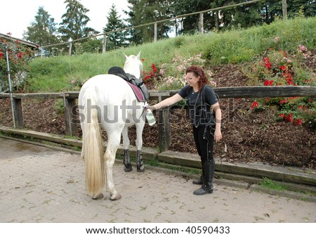 She sprinkles the horse spray against insects. - stock photo