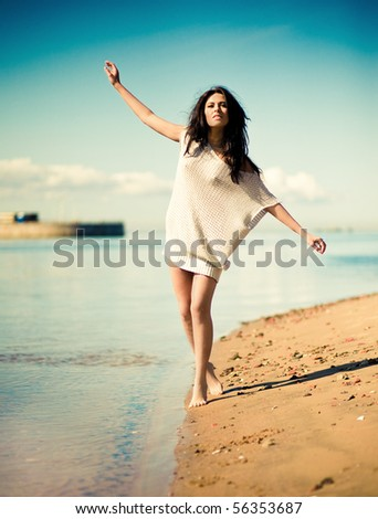 She threw up her hands at the beach - stock photo